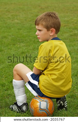 boy waiting on sidelines during a soccer game - stock photo