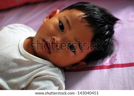 Boy wake up on the bed - stock photo