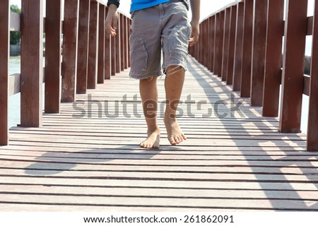 Boy walk on the red wood bridge on the sea on the day