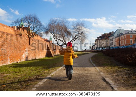 Boy walking around Warsaw Barbican fortress (castle) in spring in the capital city of Poland. Sights of Poland. Spring sunny day. Travel (vacation), architecture concept. - stock photo