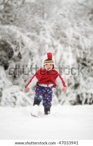 Boy walking in snow with boots on - stock photo
