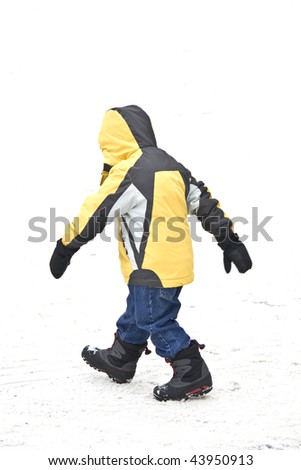 Boy walking in winter snow with yellow jacket jeans and boots. - stock photo