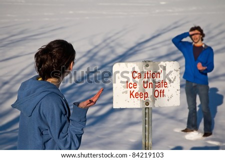Boy walking on ice, and girl is questioning his decision, based on the sign. - stock photo