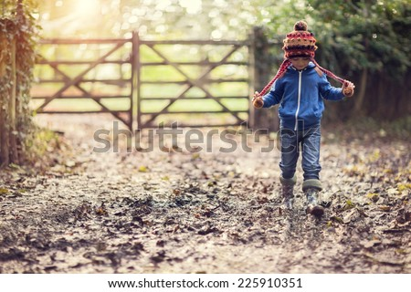 Boy walking on muddy footpath in autumn at sunset - stock photo