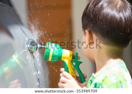boy washed car by water spray and turn his face avoid water splash