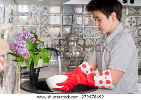 boy washing dishes  - stock photo