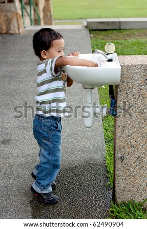 boy washing hand at outdoor sink - stock photo
