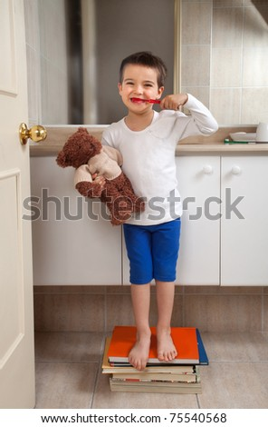 Boy washing teeth with teddy bear standing on some books in a bathroom - stock photo