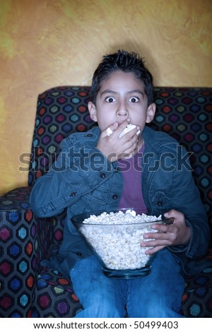 Boy watching a scary movie while eating popcorn - stock photo