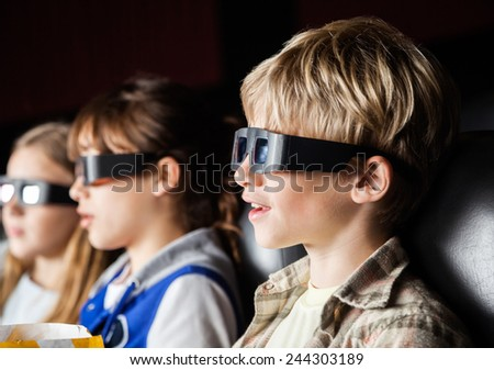 Boy watching 3D movie with siblings in cinema theater - stock photo
