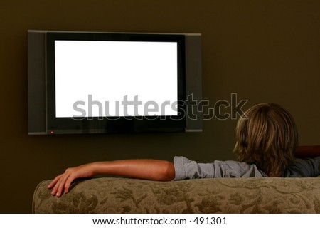 boy watching wide-screen television - stock photo