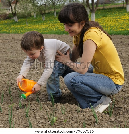 Boy watered plants with his mother - stock photo