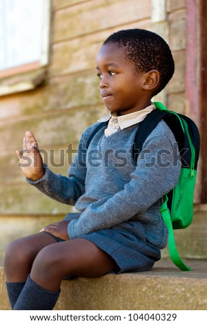 Boy waving for the citizens in town that walked past him. - stock photo