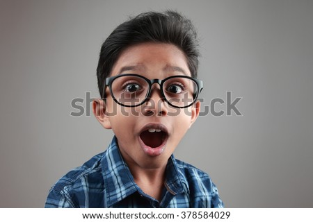 Boy wearing a big spectacle with a shocked expression - stock photo