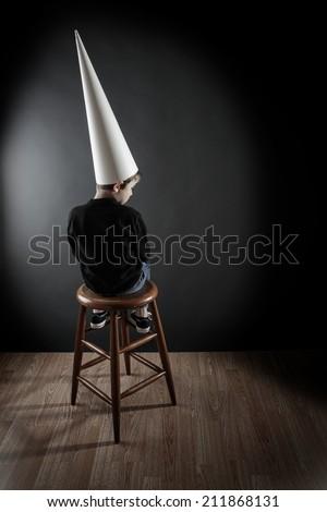 Boy wearing a dunce cap - stock photo