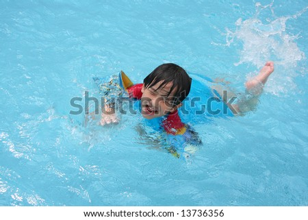 Boy wearing blue & red swim suit at the pool