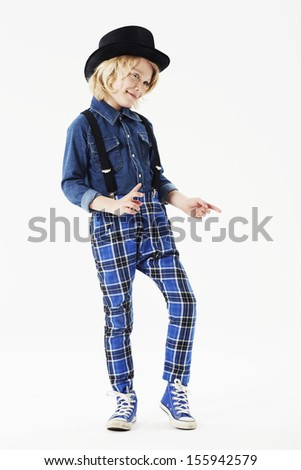 Boy wearing checked trousers and hat in studio