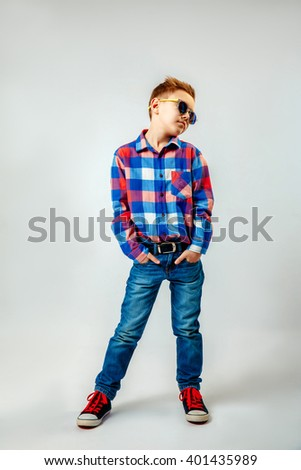 Boy wearing colorful plaid shirt, blue jeans, gumshoes, sunglasses, posing and having fun in the studio - stock photo