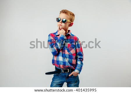 Boy wearing colorful plaid shirt, blue jeans, gumshoes, sunglasses, posing and having fun in the studio