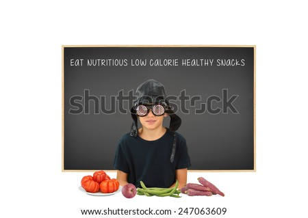 Boy wearing funny eye wear sitting at table with healthy snacks fruits, vegetables blackboard with Eat Nutritious Low Calorie Healthy Snacks - stock photo