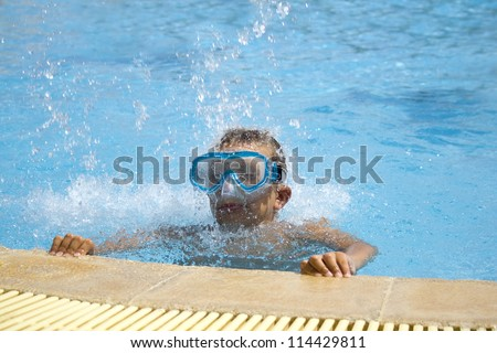 boy wearing mask in the swimming pool - stock photo
