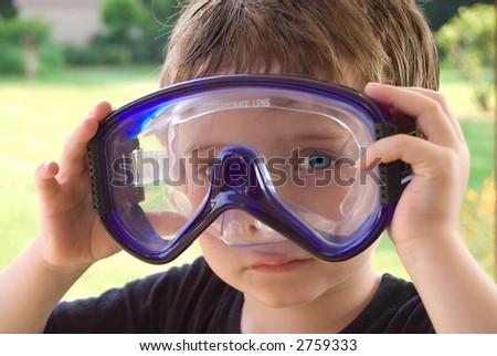 Boy wearing pool googles outside ata a pool party - stock photo