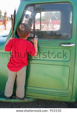 boy wearing red shirt looking in green truck - stock photo