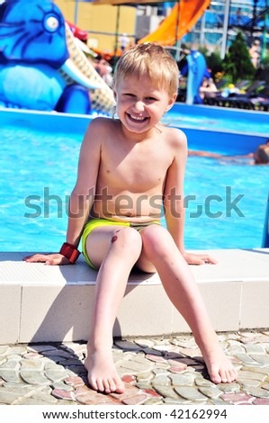 boy wearing swimming trunks is sitting close to swimming pool. summer. sunny day, boy is happy, but his kneel is already  wounded, but he is boy, so it is not unusual