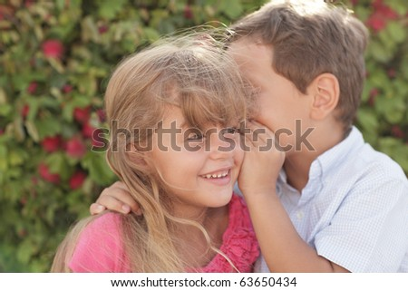 Boy whispering a secret to the girl