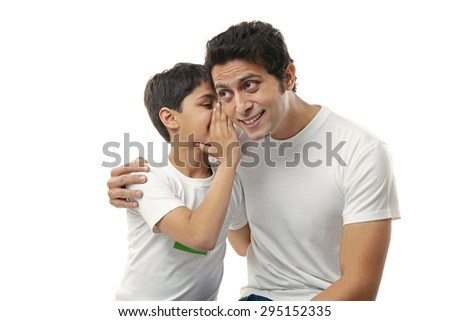 Boy whispering in his fathers ear - stock photo