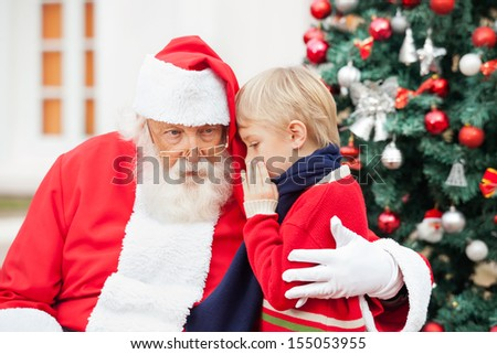 Boy whispering in Santa Claus's ear against Christmas tree - stock photo