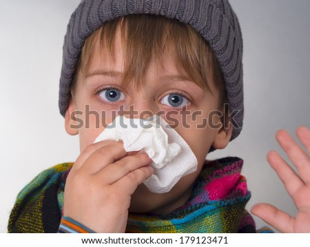 boy wiping his nose - stock photo
