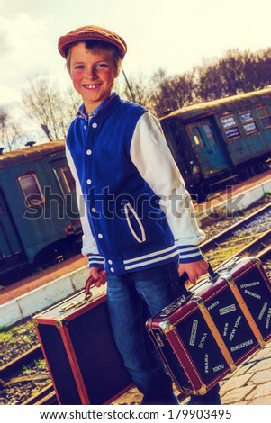 boy wit suitcases waiting for his train, vintage instagram style effect added. - stock photo