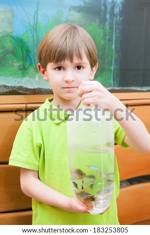 boy with a bag of fish at the aquarium - stock photo