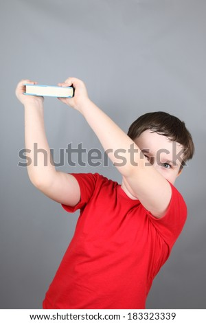 Boy with a book, gray background. - stock photo