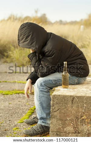 Boy with a bottle of drink, cigarettes and syringe in the foreground - stock photo