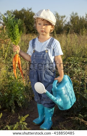 boy with a carrot and a watering can in the garden - stock photo