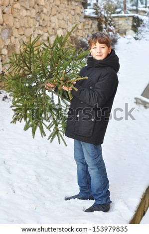 Boy with a Christmas tree - stock photo