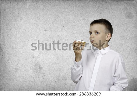 Boy with a cream cake in the hands on a gray background. - stock photo