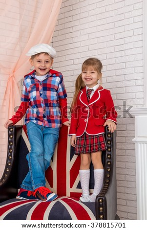 Boy with a girl sitting on a chair with a British flag