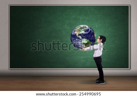 Boy with a globe of the world on the classroom - stock photo