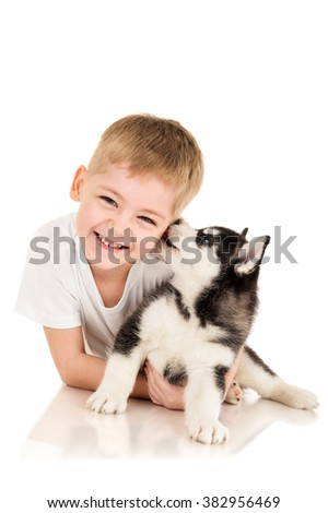 Boy with a husky puppy, isolated on white