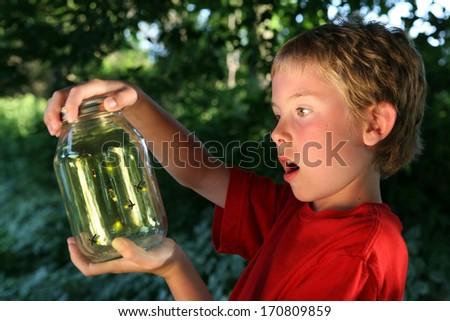 Boy with a jar of fireflies - stock photo