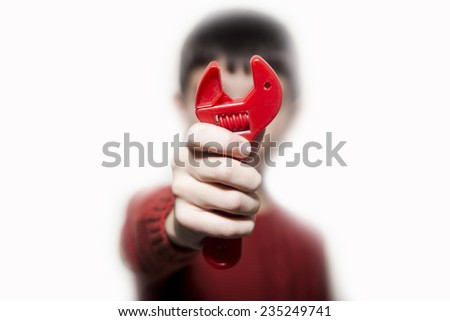 Boy with a red toy wrench on his hand. On a white background. - stock photo