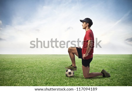 Boy with a soccer ball in large grace field - stock photo