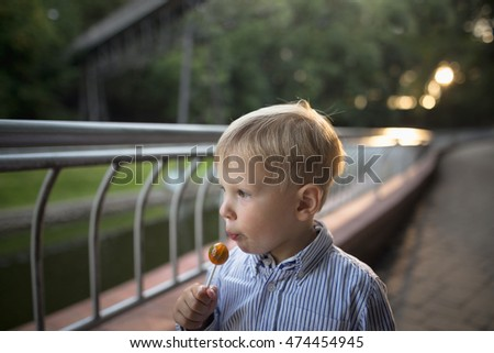 boy with a sucking candy walks in the park in the summer.