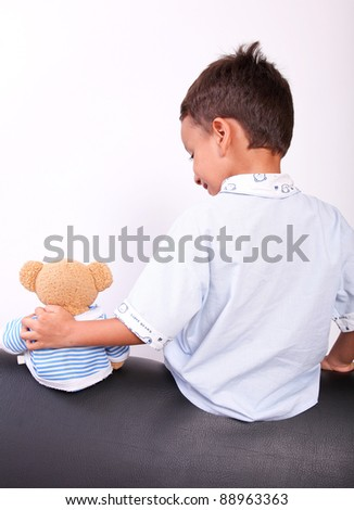 boy with a teddy bear sitting with his back
