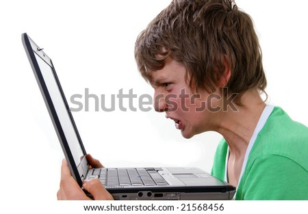 Boy with angy expression in front of computer - stock photo