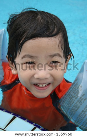 boy with arm float in the pool - stock photo
