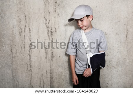 Boy with arm in a sling from a broken humerus wearing a baseball - stock photo